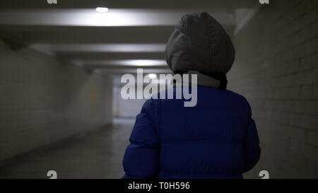 teenager boy walks through a narrow dark tunnel in winter, holds something in his hand, back view - Stock Photo