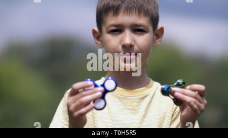 Happy Boy holding play two fidget spinners on nature - Stock Photo