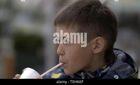 boy drinks a milkshake at a cafe outdoors - Stock Photo