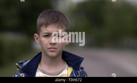 portrait of a serious boy with a tence glance looking at the camera, close-up heavy face - Stock Photo