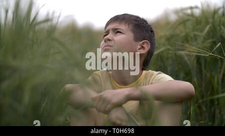 serious boy with a tence glance is sitting in the field looking at the sky - Stock Photo