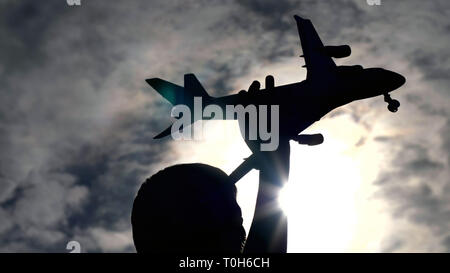boy playing with toy airplane against beautiful sky - Stock Photo