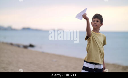 enthusiastic boy playing with paper airplane near the sea in the evening - Stock Photo