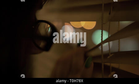 young brunette with glasses with a black rim pushes the blinds with her hand with a manicure looks at the window - Stock Photo