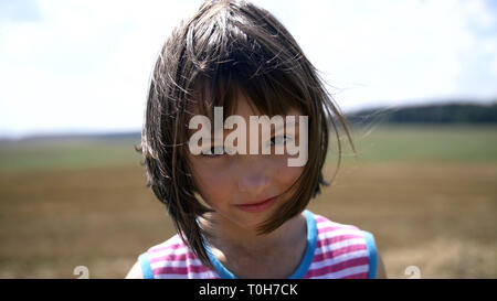 portrait of a young girl looking at the camera in nature - Stock Photo