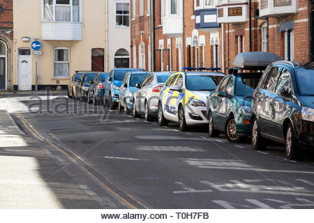 View of very tightly parked cars in a residential side street in Weymouth, Dorset, England, - Stock Photo