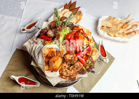Mixed grill meat, fried vegetables and grilled salmon fish fillets decoration in warm dish. Assorted delicious grilled kebab served with herbs on plat - Stock Photo