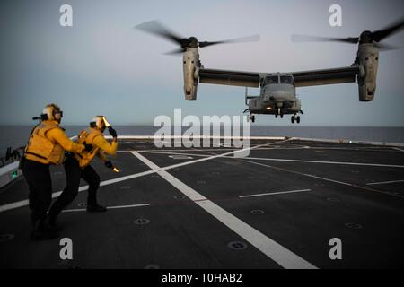PACIFIC OCEAN (March 16, 2019) – Aviation Boatswain's Mate (Handling) Airman Brian Bickmeier directs the landing of an MV-22B Osprey from Marine Medium Tiltrotor Squadron 164 on the flight deck of USS New Orleans (LPD 18) during exercise Pacific Blitz 19.  Pacific Blitz is a scenario-driven joint exercise that provides relevant training by replicating a realistic maritime threat environment designed to challenge and improve amphibious capabilities necessary for effective global crisis response.  (U.S. Navy photo by Mass Communication Specialist 2nd Class Kelby Sanders) - Stock Photo