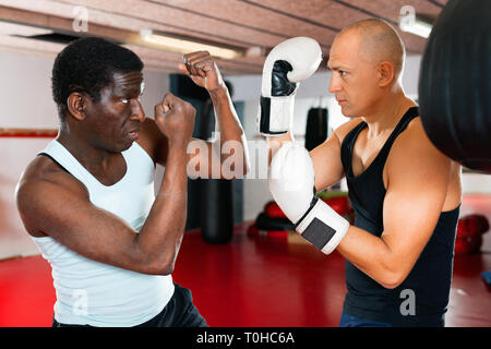 Glad cheerful positive african american trainer teaches man in boxing - Stock Photo