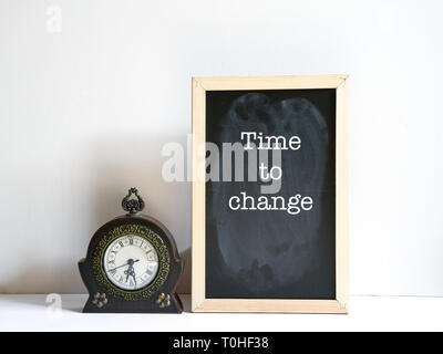 Time to change concept - message on board with an antique clock by the side - Stock Photo