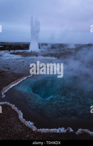 Strokkur geyser erupting in the distance with the clear water of Blesi geyser in the foreground, drawing your eye into its crystal clear depths! - Stock Photo