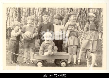 1960's postcard of group of happy young British children, boys and girls and toddler, aged from 2 to 4 years old playing outdoors, with bike and pull along cart, U.K. - Stock Photo
