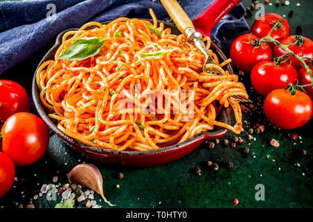 Italian lunch. Homemade spaghetti pasta with classic marinara tomato sauce, spices, garlic, basil. On a dark green concrete table copy space - Stock Photo
