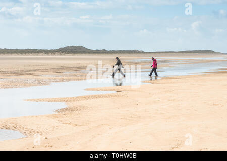 Hikers cross water pools left by the tide on sandy beach at Holkham bay, North Norfolk coast, East Anglia, England, UK. - Stock Photo