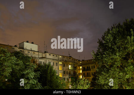 Buildings and green trees at night, illuminated sky in summer - Stock Photo