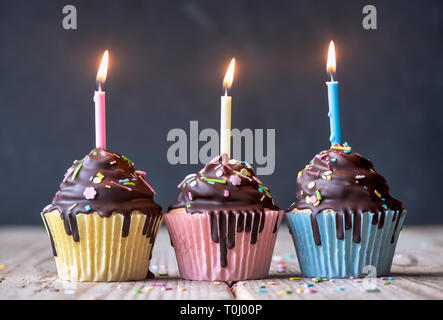 Birthday cupcakes with candles. Vanilla cupcakes with a meringue frosting and dark chocolate shell - Stock Photo