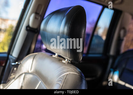 Leather car headrest illuminated by the sun, inside the used car, visible signs of use. - Stock Photo
