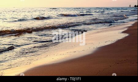 Beach Sunset With Waves Crashing Up On Shore, During The Summer Months On Lake Huron In Ontario Canada. - Stock Photo