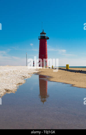 Reflections of the Kenosha North Pier Lighthouse as the Spring sun melts the remaining snow. - Stock Photo