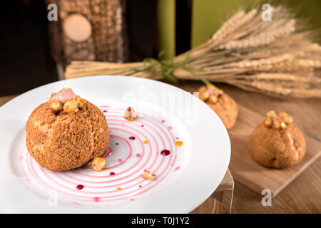 Homemade violet profiterole served in white plate. - Stock Photo
