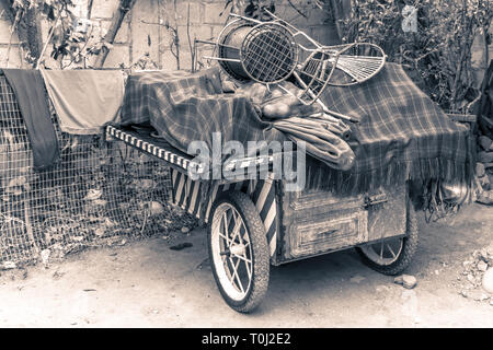 Old sales cart. Piled up with disused objects - Stock Photo