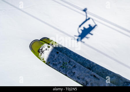 Skis above skiers shadows in chairlift above the white snow, during a Winter ski vacation in Les Sybelles, French Alps. Abstract ski concept with shad - Stock Photo
