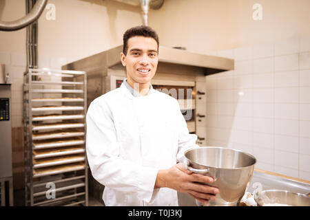 Young dark-eyed man feeling happy working in nice bakery - Stock Photo