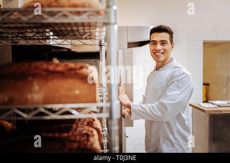 Dark-eyed baker smiling after baking nice yummy bread - Stock Photo