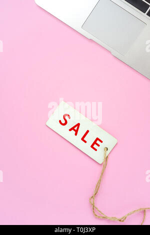 Sale tag and laptop on pink background, online shopping concept - Stock Photo