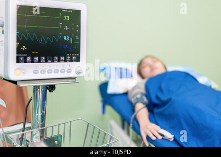 Nurse taking Asian young woman's blood pressure in ER room at hospital. - Stock Photo