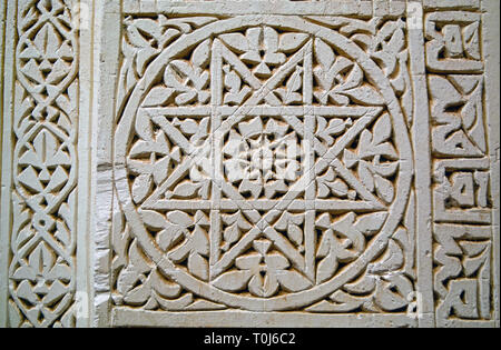 Closeup of an Islamic geometrical pattern carved in light coloured stone (a star inside a circle) with calligraphy on the right side. - Stock Photo
