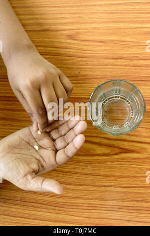 Self-treatment at home as per prescribed by doctor. A teenager boy pouring medicine into her hand. Medical, health care or people concept. High Angel  - Stock Photo