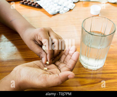 Self-treatment at home as per prescribed by doctor. Close up of a man pouring medicine into his hand. Medical, health care or people concept. Side Ang - Stock Photo