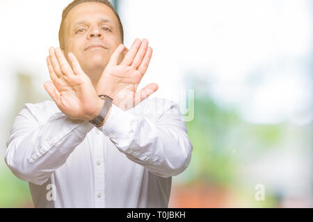 Middle age arab elegant man over isolated background Rejection expression crossing arms and palms doing negative sign, angry face - Stock Photo