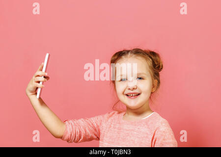 Closeup portrait of a cute little girl with buns of hair on a pink background. The child holds the phone and takes a selfie - Stock Photo