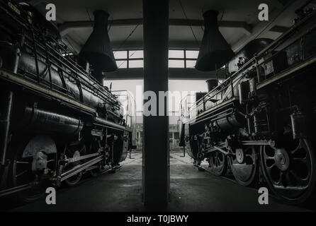 Two locomotives sit in the engine shed at Kyoto Railway Museum. - Stock Photo