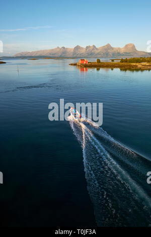 Exploring the many islands and coastline summer seascape of Heroy and Alsta and the distant Seven Sisters mountain range in Helgeland Nordland Norway