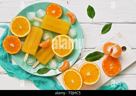Popsicle orange with slices of fresh orange, mandarin and green leaves on a white rustic plank table. Top view, flat lay. - Stock Photo