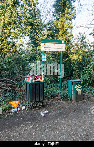Overflowing rubbish bins on Parkland Walk, a disused railway line, now a nature reserve, in North London, UK - Stock Photo