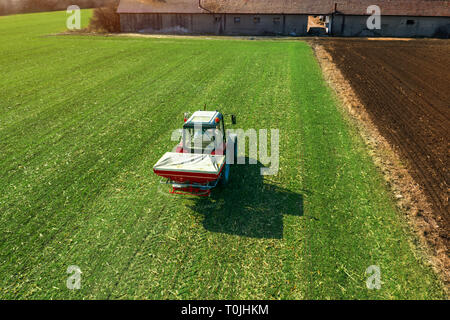 Unrecognizable farmer in agricultural tractor is fertilizing wheat crop field with NPK fertilizers, aerial view from drone pov - Stock Photo