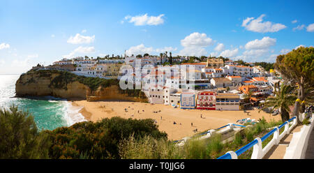 View of the sandy beach surrounded by typical white houses on a sunny spring day, Carvoeiro, Lagoa, Algarve, Portugal. - Stock Photo