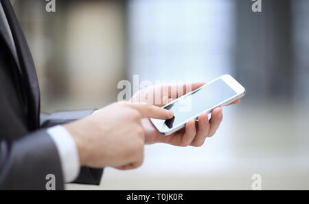 close up.the businessman clicks on the smartphone screen - Stock Photo