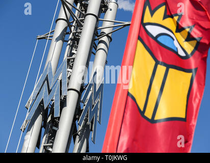 Leipzig, Germany. 20th Mar, 2019. A flag with the logo of the Leipzig Book Fair is flying in front of the trade fair logo on the exhibition grounds. The Leipzig Book Fair 2019 will open in the evening with a ceremonial act. Until Sunday (24.03.2019) about 2600 exhibitors will present themselves on the exhibition grounds. At the same time the festival 'Leipzig reads' invites to numerous readings. The guest country of the Book Fair this year is the Czech Republic. Credit: Jan Woitas/dpa-Zentralbild/dpa/Alamy Live News - Stock Photo