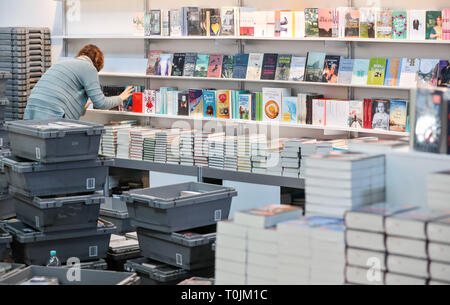 Leipzig, Germany. 20th Mar, 2019. An employee equips the shelves of the trade fair bookstore for the Leipzig Book Fair. The Leipzig Book Fair 2019 will open in the evening with a ceremonial act. Until Sunday (24.03.2019) about 2600 exhibitors will present themselves on the exhibition grounds. At the same time the festival 'Leipzig reads' invites to numerous readings. The guest country of the Book Fair this year is the Czech Republic. Credit: Jan Woitas/dpa-Zentralbild/dpa/Alamy Live News - Stock Photo