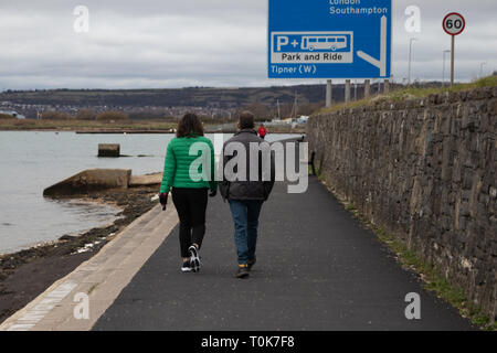 Couple walking along the shore with motorway sign in backgorund - Stock Photo