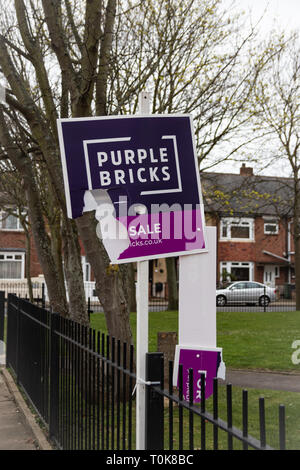 Ripped and broken Purple bricks estate agents for sale or sold sign - Stock Photo