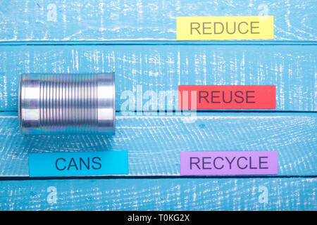 Recycle concept showing reduce, reuse, recycle with cans on a blue weathered background - Stock Photo