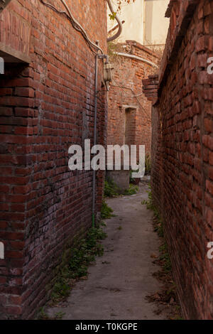 View through narrow alley with red brick buildings wandering in Lukang old street, Lukang Township, Changhua County, Taiwan - Stock Photo