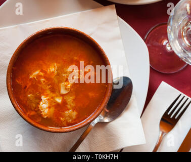 Top view of clay bowl of Castilian garlic soup rich with bread, stringy egg and punchy broth. Spanish cuisine - Stock Photo