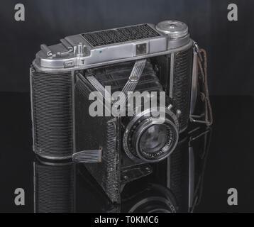 Nostalgic photo of old camera. A mirror table. Dark tonality. - Stock Photo